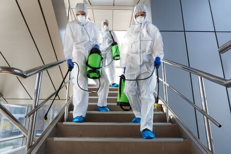 Photo for People wearing protective suits disinfecting stairs with spray chemicals to prevent the spreading of the coronavirus - Royalty Free Image
