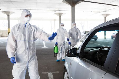 Photo for Men in hazmat suits stopping and disinfecting cars of coronavirus cells, world epidemic, quarantine - Royalty Free Image