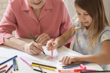 Photo pour Family activities. Mature woman with her lovely granddaughter drawing Christmas tree together in kitchen - image libre de droit