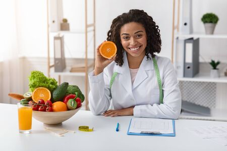 Photo pour Modern dietologist african woman sitting at workplace and recommending fresh oranges - image libre de droit