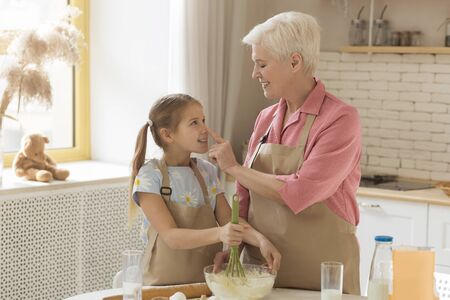 Photo pour Time for cooking. Grandmother with her little granddaughter having fun while baking in sunlit kitchen, blank space - image libre de droit