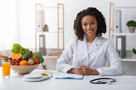 Photo pour Attractive young black woman nutritionist posing at her modern office, copy space - image libre de droit