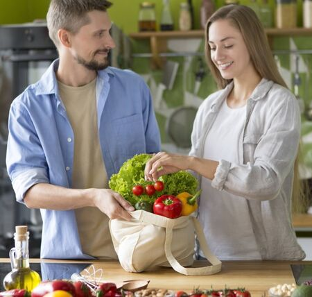 Photo for Young beautiful couple in kitchen cooking vegetarian healthy dishes together, quarantine time - Royalty Free Image