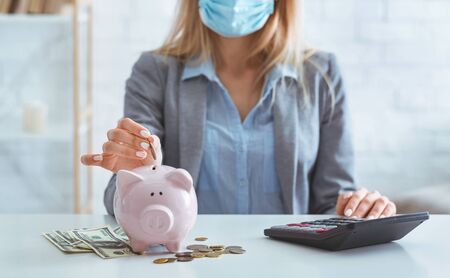 Photo pour Girl in protective mask saves money in bank pig during quarantine - image libre de droit