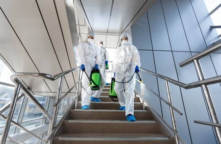 Photo for Government workers in protective suits making disinfection of stairs and surfaces from coronavirus, preventive measures, copy space - Royalty Free Image