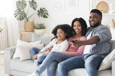Photo pour Smiling african american family relaxing and watching tv in living room, staying at home during quarantine, happy father switching channels - image libre de droit