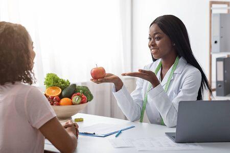 Photo pour Positive african woman nutritionist recommending female patient fresh fruits to eat, clinic interior - image libre de droit
