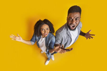 Top View Of Angry Black Couple Emotionally Reacting To Something, Objecting With Raised Hands, Standing Together On Yellow Studio Background