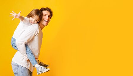 Photo pour Positive dad holding his happy daughter on his back, imitating airplane, yellow background, panorama with empty space - image libre de droit