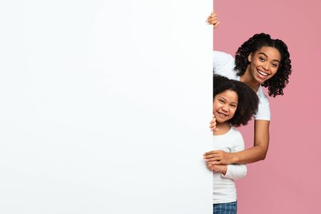 Photo pour Family Offer. Happy African American Mother And Preschool Daughter Peeking Out Of Blank White Board With Free Space For Your Ad Over Pink Background - image libre de droit
