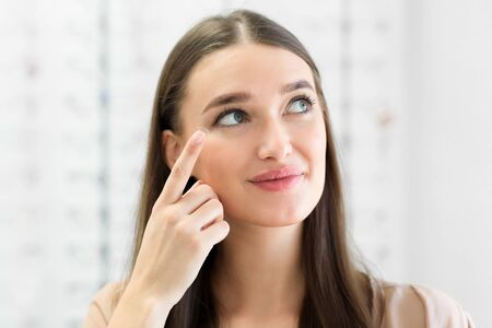 Photo pour How To Apply Contact Lenses Concept. Close up portrait of young woman wearing eye lens, looking aside - image libre de droit