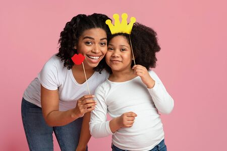 Photo for Party Fun. Portrait Of Happy Afro-American Mother And Her Little Daughter Posing With Paper Accessories, Holding Lips And Crown On Sticks - Royalty Free Image
