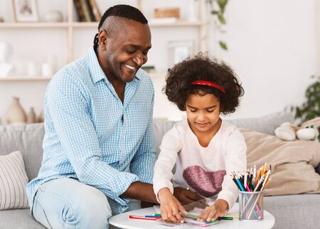 Photo pour Family pastimes. Happy African American grandfather and his lovely granddaughter drawing together at home - image libre de droit