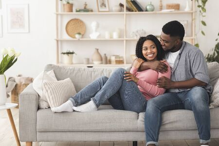 Photo pour Stay At Home. Young African American Couple In Love Cuddling On Couch In Living Room, Enjoying Spending Time Together, Free Space - image libre de droit