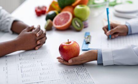 Photo pour Close up of dietologist and patient female hands over doctor workplace, nutritionist holding apple - image libre de droit
