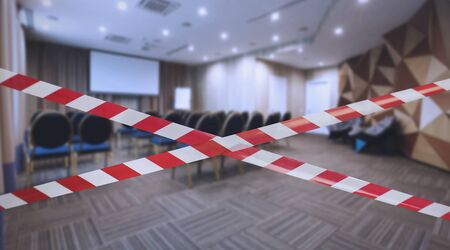 Photo for Quarantine Zone Warning Tape, Do Not Cross. Red and white hazard safety stripes across empty closed conference hall - Royalty Free Image
