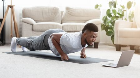 Foto de Home Workout. Sporty Young Black Man Making Fist Plank Exercise In Front Of Laptop, Watching Fitness Tutorials Online, Panorama - Imagen libre de derechos