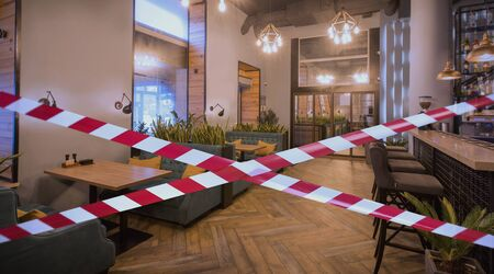 Photo for Quarantine Zone Warning Tape, Do Not Cross Concept. Red and white hazard safety stripes across empty closed cozy restaurant - Royalty Free Image