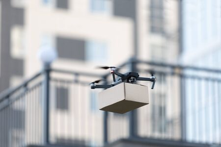 Foto für New smart drone with parcel, package delivery robot. Contactless air remote transportation, blurred background - Lizenzfreies Bild