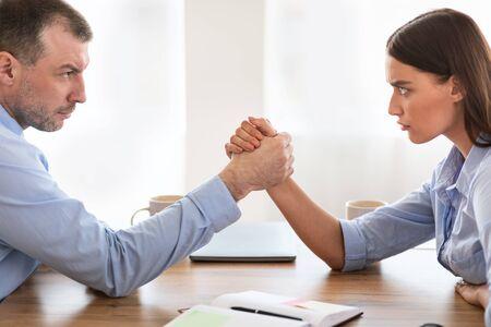 Photo pour Businessmen Vs Businesswomen Competition. Businessman And Businesswoman Arm Wrestling Arguing Whos Stronger Sitting At Work Desk In Modern Office. - image libre de droit