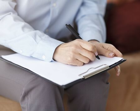 Photo pour Unrecognizable Professional Psychologist Taking Notes Holding Folder Sitting On Couch In Office. Cropped, Closeup - image libre de droit