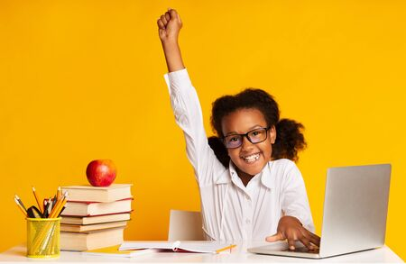 Photo pour Online Classes. Happy African Schoolgirl At Laptop Raising Hand During Distant Lesson Learning From Home. Yellow Background, Studio Shot - image libre de droit