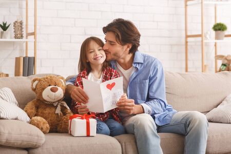 Photo pour The best present is you. Happy daddy kissing his smiling little daughter on Father Day, home interior, copy space - image libre de droit