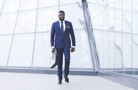 Photo pour Successful Business People. African Businessman With Briefcase Walking In Urban Area In City. Full Length, Copy Space - image libre de droit
