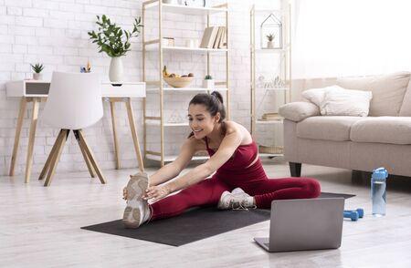 Photo pour Female yoga instructor running online training session via laptop at home - image libre de droit