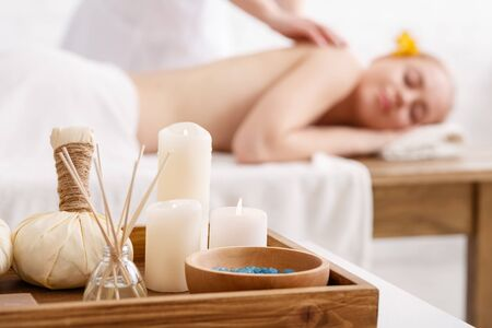 Foto de Ayurvedic massage. Salt, candles, aromatic sticks and bags with herbs, close up, professional doing massage to girl on table - Imagen libre de derechos