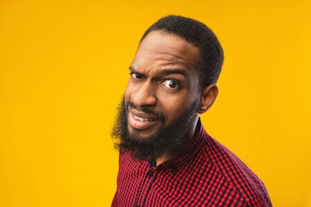 Photo pour Close up headshot of confused african american man looking at camera with raised eyebrow, yellow studio wall - image libre de droit