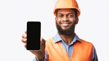 Photo pour Black Builder Workman Showing Smartphone Blank Screen Standing Over White Studio Background. Panorama, Mockup, Selective Focus - image libre de droit