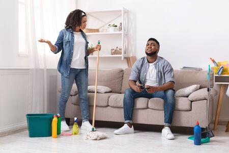 Photo pour Household Chores Problem. Displeased African Woman Blaming Her Lazy Husband Playing Video Games While She Cleaning - image libre de droit