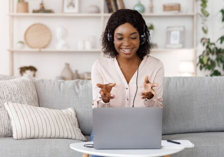 Foto de Online Tutoring Concept. Smiling black female tutor having video call with student, giving language class by webcam, sitting on couch at home - Imagen libre de derechos