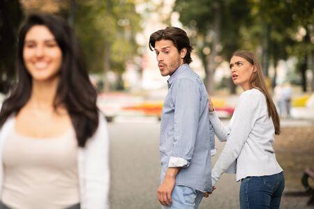 Photo pour Jealousy. Jealous Girlfriend Calling Boyfriend Distracted By Other Attractive Woman Walking During Date In Park. Selective Focus - image libre de droit