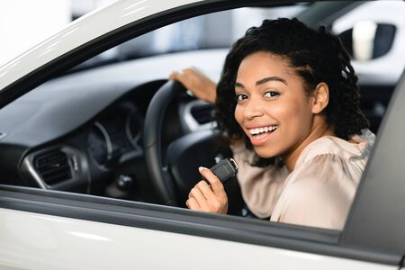 Photo for New Car Concept. Joyful Black Lady Buyer Showing Auto Key Sitting In Drivers Seat In Automobile In Dealership. Selective Focus - Royalty Free Image