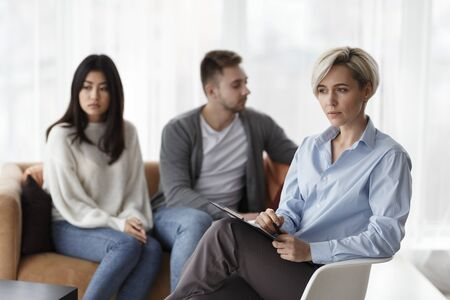 Photo pour Family Counseling. Pensive Psychologist Thinking How To Help Unhappy Married Couple Save Marriage Sitting In Office. Selective Focus - image libre de droit