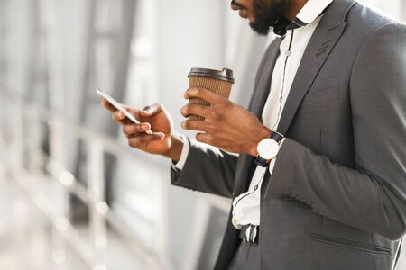 Photo pour Waiting For Flight. Unrecognizable Black Businessman Using Smartphone Having Coffee Standing In Airport Indoors. Cropped, Selective Focus - image libre de droit