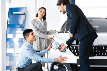 Photo pour Special Offer. Car vendor showing brand-new vehicle to young couple, spouses examining auto - image libre de droit