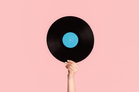 Photo pour Girl hand showing retro vinyl gramophone record on pink background, close up - image libre de droit