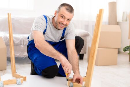 Photo pour Happy Repairman Assembling Furniture Installing Table After Transportation In New Home, Smiling To Camera Indoor. Furnishing And Assembly Services. - image libre de droit