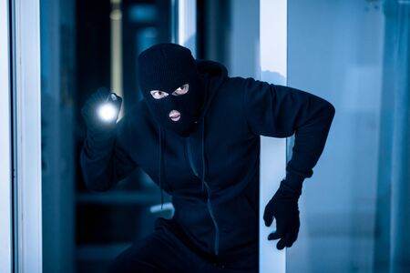 Photo pour Stealthy criminal wearing black balaclava sneaking into house through window or glass door, using torch at night - image libre de droit