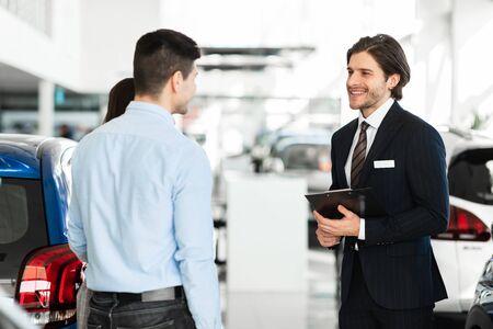 Photo pour Car Sale. Handsome salesperson holding clipboard talking to young family, showing vehicles - image libre de droit