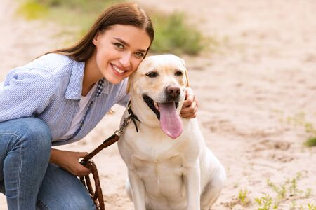 Photo for Pets Love Concept. Beautiful girl posing at camera with her cute dog during walk, copy space, blurred background - Royalty Free Image