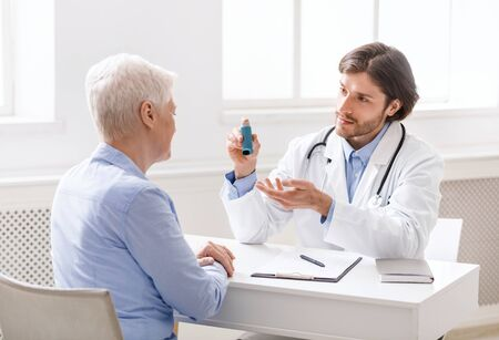 Photo pour Doctor explaining pills schedule to senior patient during appointment at clinic - image libre de droit
