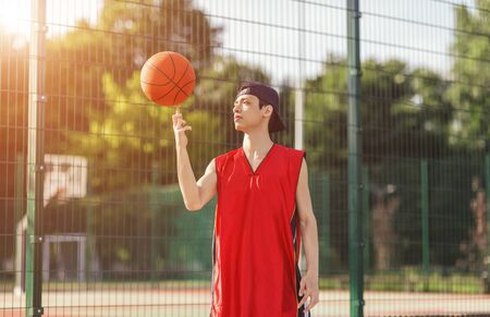 Young Asian basketball player with ball on outdoor court