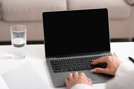 Foto de Search in internet and work at home. Female hands typing on laptop with blank screen - Imagen libre de derechos