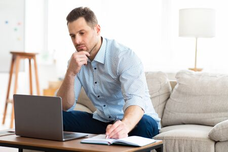 Photo pour Self Education At Home. Concentrated man holding pen and looking at laptop sitting in living room, free space - image libre de droit