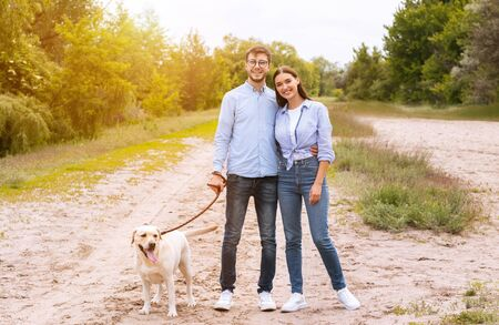 Photo for Family Portrait Concept. Casual boyfriend and girlfriend walking their labrador retriever in forest, posing at camera - Royalty Free Image