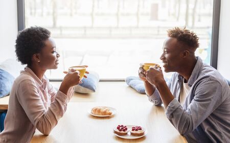 Photo pour Side view of black boyfriend and girlfriend enjoying their coffee at cafe - image libre de droit